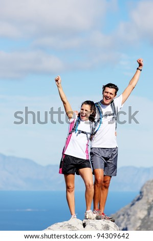 Hiking couple happy to reach the top of a mountain, healthy happy outdoor lifestyle - stock photo