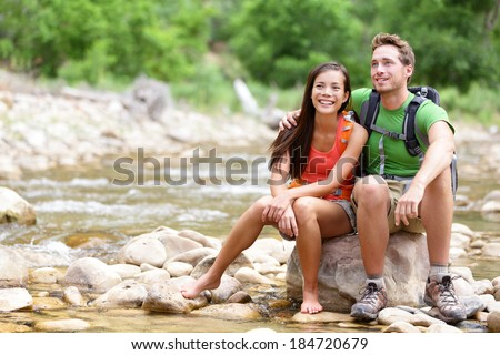 Hiking couple - hikers resting in Zion National Park. Young woman and man hiker sitting by river water creek enjoying view smiling happy. Young couple trekking, relaxing after hike, Utah, USA.