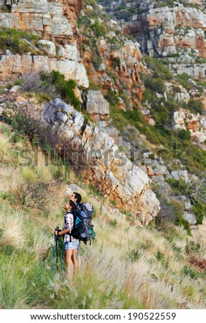 Hiking couple looking up at large mountain range - stock photo