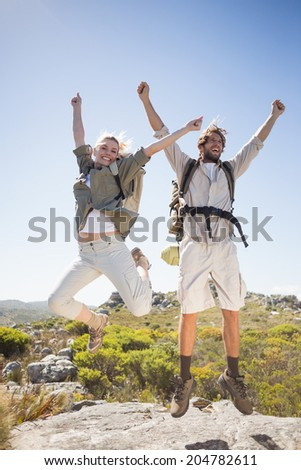 Hiking couple standing on mountain terrain cheering and jumping on a sunny day