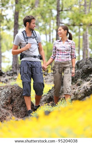 Hiking couple walking in forest. Young hikers couple enjoying romantic walk in spring forest with flower. Happy smiling interracial couple holding hands during hike in Tenerife, Canary Islands, Spain - stock photo