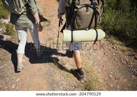 Hiking couple walking on mountain terrain on a sunny day - stock photo