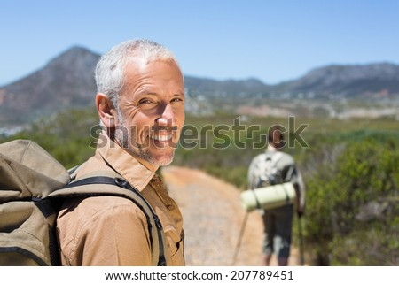 Hiking couple walking on mountain trail man smiling at camera on a sunny day - stock photo