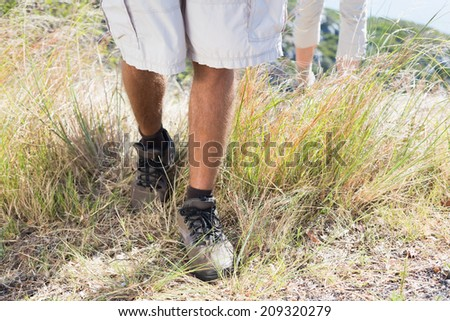 Hiking couple walking on mountain trail on a sunny day - stock photo