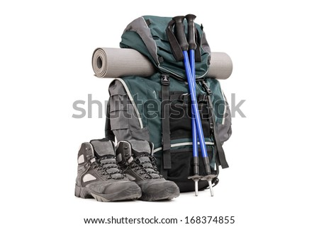 Hiking equipment, rucksack, boots, poles and slipping pad isolated on white background - stock photo