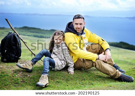 Hiking family adventure on mountain trek: beauty kid girl and her  active father in jackets and special boots having rest on green lawn with mountain lake view: Scotland, Skye