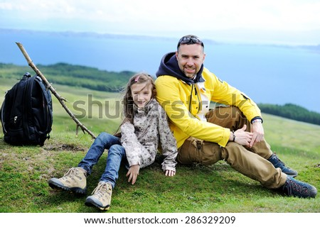 Hiking family adventure on mountain trek: beauty kid girl and her  active father in jackets and special boots having rest on green lawn with mountain lake view: Scotland, Skye - stock photo