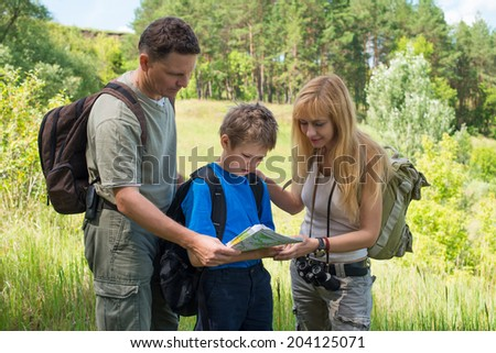 Hiking family with backpacks in the forest discussing the route. Happy couple with son looking at the map.  - stock photo