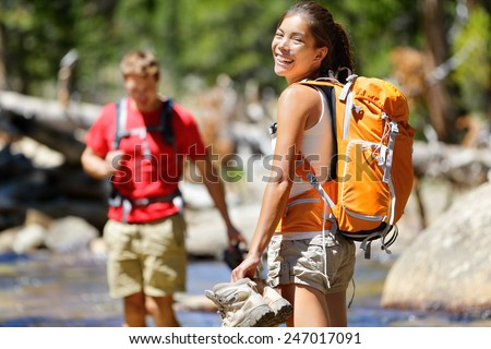 Hiking friends having fun crossing river in forest. Young happy adults barefoot walking in water with wet feet on an adventure trip hike in nature. - stock photo