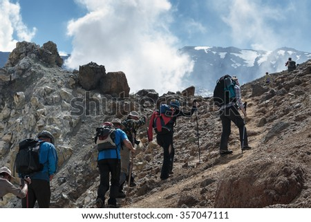 Hiking group of people on a tourist track climb the steep slope to the crater of active Mutnovsky Volcano on sunny day. Eurasia, Far East, Russia, Kamchatka Peninsula. - stock photo