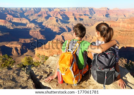 Hiking hikers in Grand Canyon enjoying view of nature landscape. Young couple relaxing during hike wearing backpacks on South Kaibab Trail, south rim of Grand Canyon, Arizona, USA. - stock photo