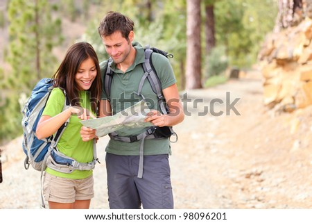 hiking - hikers looking at map. Couple or friends navigating together smiling happy during camping travel hike outdoors in forest. Young mixed race Asian / Caucasian woman and Caucasian man. - stock photo