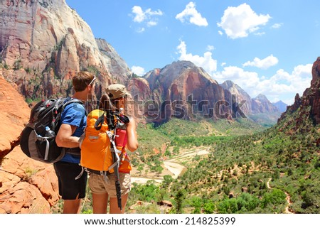 Hiking - hikers looking at view in Zion National park. People living healthy active lifestyle dong hike in beautiful nature landscape to Observation Point near Angles Landing, Zion Canyon, Utah, USA. - stock photo