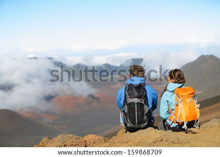 Hiking - hikers sitting enjoying view on volcano. Hiker couple looking at beautiful nature landscape of mountain, East Maui Volcano, Haleakala national park Hawaii, USA. People resting and relaxing. - stock photo