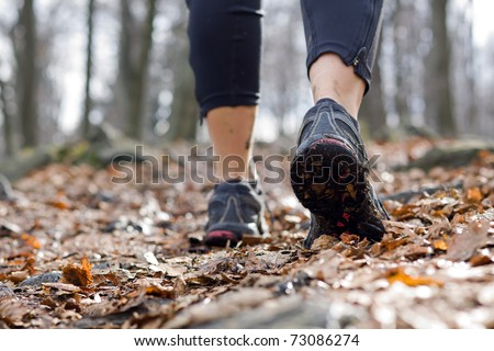 Hiking in autumn forest, sport shoes closeup - stock photo