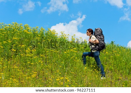 Hiking in the grass, sky background - stock photo