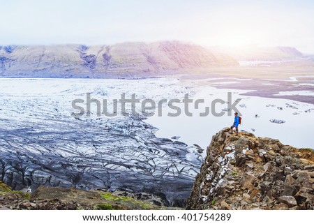 hiking in winter, backpacker enjoying panoramic landscape of glacier in Iceland at sunset in national park Skaftafell - stock photo