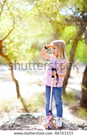 hiking kid girl searching hand in head in forest outdoor - stock photo