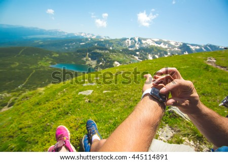 Hiking man checking direction in mountains by smartwatch. - stock photo