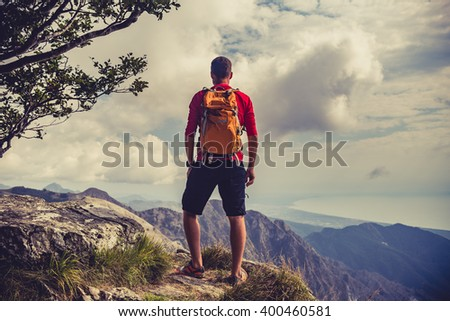 Hiking man, climber or trail runner in mountains, inspirational landscape. Motivated hiker with backpack looking at beautiful view. Trekking, travel and tourism concept. Fitness and healthy lifestyle. - stock photo