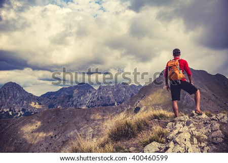Hiking man, climber or trail runner in mountains, inspirational landscape. Motivated hiker with backpack looking at beautiful view. Travel, fitness and healthy lifestyle outdoors in summer nature. - stock photo