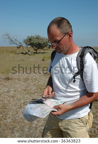 Hiking man in Africa with compass and map