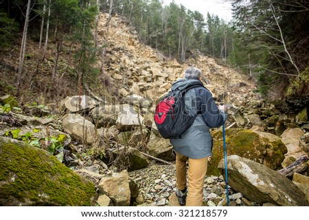 Hiking man in mountain over dark rocking mountain