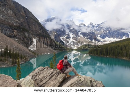 Hiking man sitting down with rucksack backpack on a rock by Moraine Lake looking at snow covered Rocky Mountain peaks, Banff National Park, Alberta Canada - stock photo