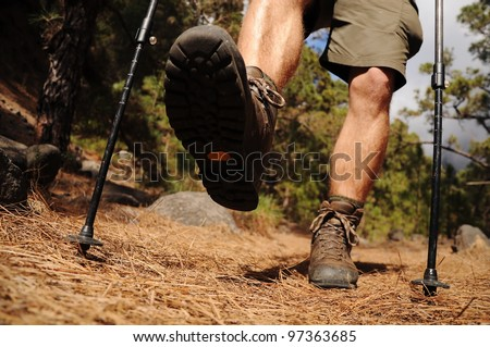 Hiking man with trekking boots on the trail - stock photo