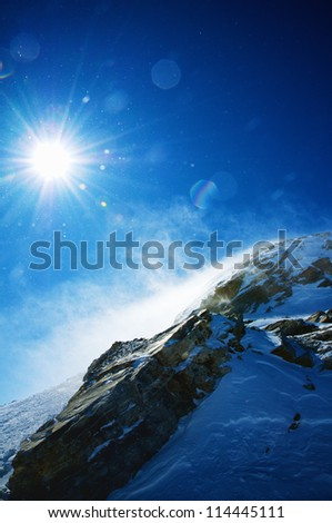 hiking mountain during snow storm with blue sky. - stock photo