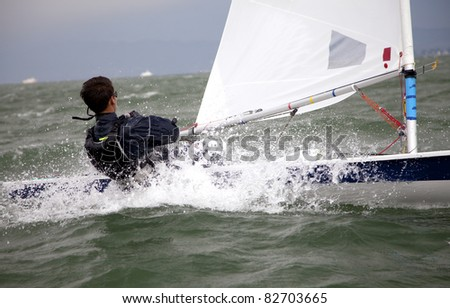 hiking out on a small sailboat - stock photo