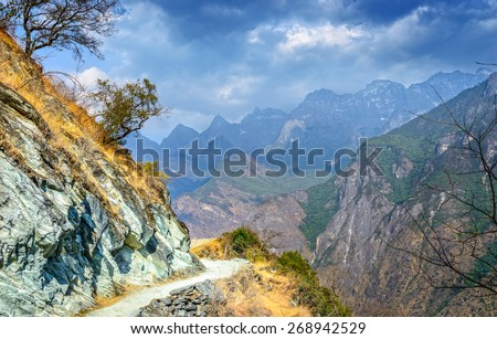 Hiking path (the high road) of Tiger Leaping Gorge. Located 60 kilometres north of Lijiang City, Yunnan Province, China.  - stock photo