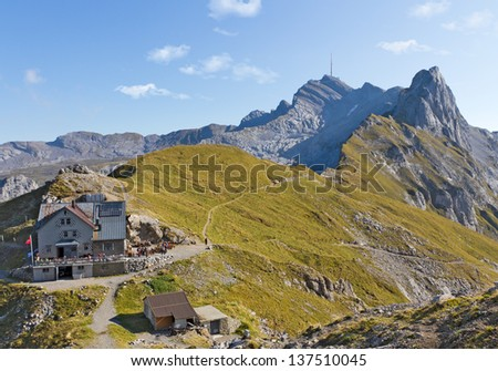 hiking path through rocky mountainous ridges with rest house and leading up mountain Saentis, Switzerland - stock photo