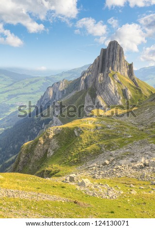 hiking path through rocky mountainous terrain with sharp rock formations in the background, Switzerland - stock photo