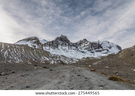 Hiking path to Athabasca Glacier with Mount Andromeda and Mount Athabasca on a overcast morning. Majestic mountains in the Canadian Rockies - stock photo