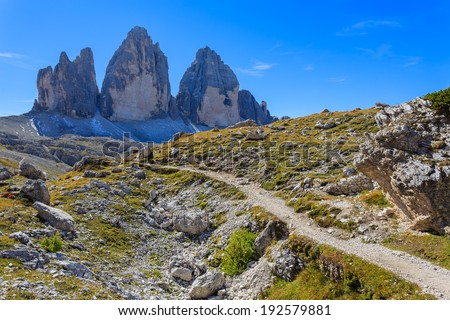 Hiking path with view of Tre Cime di Lavaredo famous rock formation, Dolomites Mountains, Italy  - stock photo
