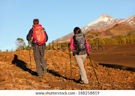 Hiking people - healthy active lifestyle couple. Hikers walking away in rear back view in beautiful mountain landscape. Woman and man walking on hike on volcano Teide, Tenerife, Canary Islands, Spain.