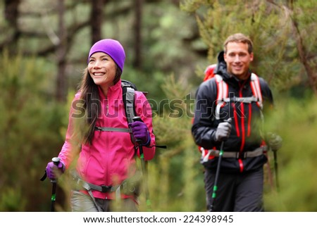 Hiking people - hikers trekking in forest on hike. Couple on adventure trek in beautiful forest nature. Multicultural Asian woman and Caucasian man living healthy active lifestyle in woods. - stock photo