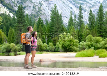 Hiking people on hike in mountains in Yosemite. Hikers young couple pointing looking up in mountain landscape in Yosemite National Park, California, USA. Multicultural couple active outdoors. - stock photo