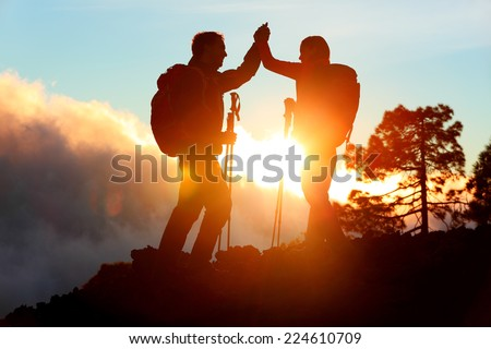 Hiking people reaching summit top giving high five at mountain top at sunset. Happy hiker couple silhouette. Success, achievement and accomplishment people - stock photo