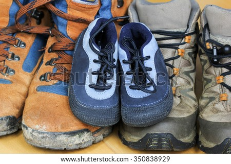 Hiking shoes from father, mother and baby - family concept - stock photo