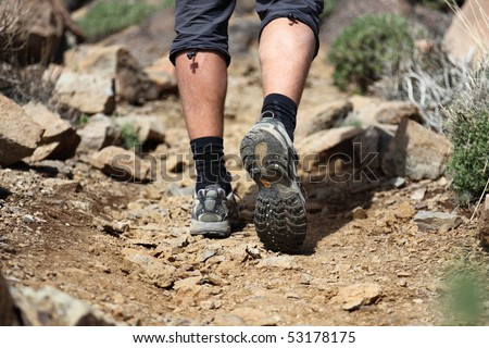 hiking shoes in action on a mountain desert trail path. Close-up of male hikers shoes. Photo is from Tenerife.