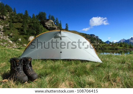 Hiking shoes in front of a tent at a campsite in the mountains. - stock photo