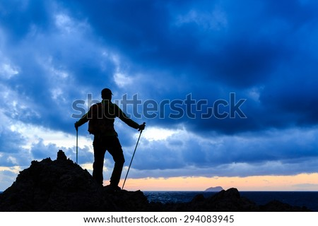 Hiking silhouette backpacker on top, man looking at inspirational ocean and island, relaxing or camping in mountains on mountain peak. Motivation for fitness and healthy lifestyle outdoors in nature. - stock photo
