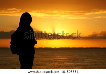 Hiking teenager looking out over the sunset - stock photo