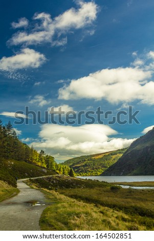 Hiking through Glendalough upper lake on a sunny day, County Wicklow, Ireland - stock photo