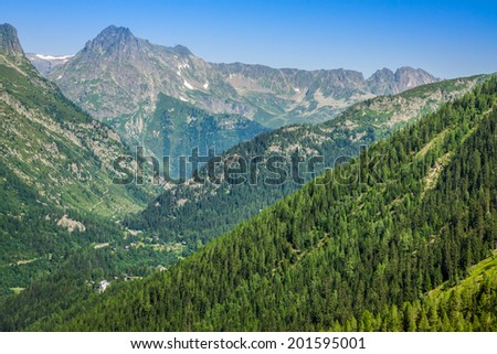 Hiking to Argentiere glacier with the view on the massif des Aiguilles Rouges in French Alps - stock photo