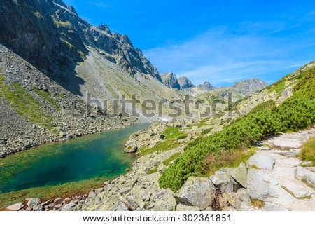 Hiking trail along beautiful lake in summer landscape of Starolesna valley, High Tatra Mountains, Slovakia - stock photo