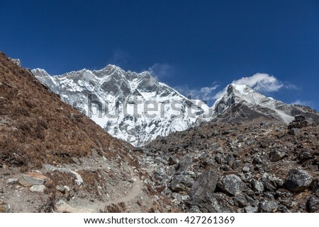 Hiking trail in Everest Base Camp Trek with Lhotse South Face wall on the horizon. Extreme hicking trail in Himalayan mountains. Rocky hiking trail on a bright sunny day. Adventure hiking trail. - stock photo
