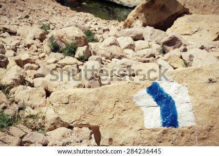 Hiking trail marker painted on a stone in rocky desert area. Photographed at Nahal Arugot, Ein Gedi, Israel. - stock photo